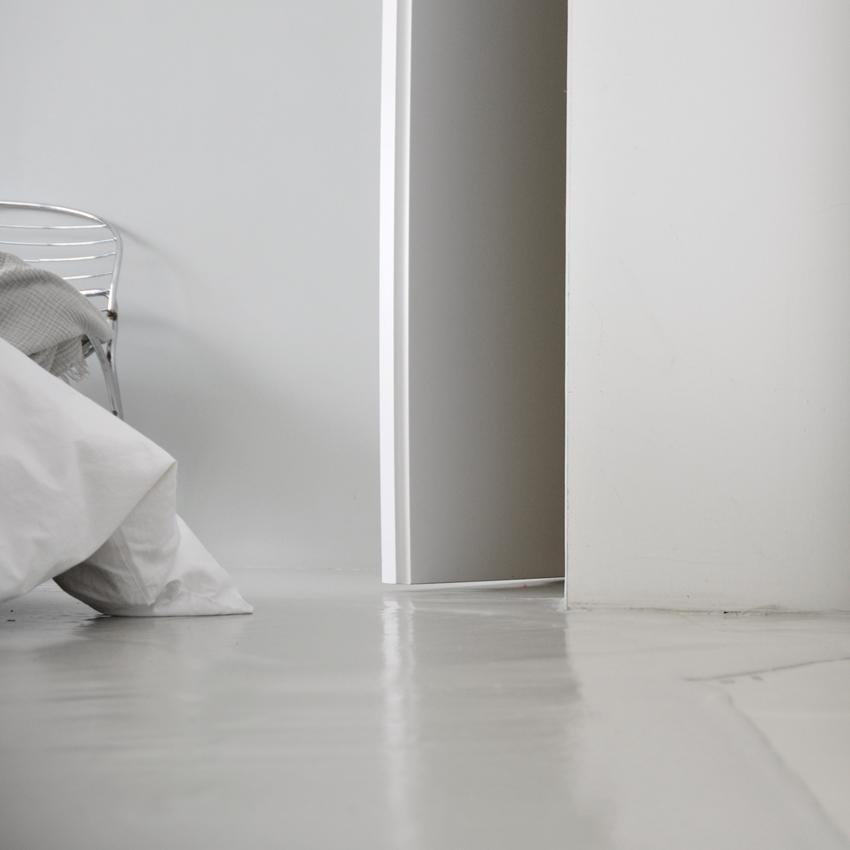 Schlafzimmer Boden gespachtelt grau Zement Bettdecke weiß - Mut zur Farbe | Ein Schlafzimmer in Grün