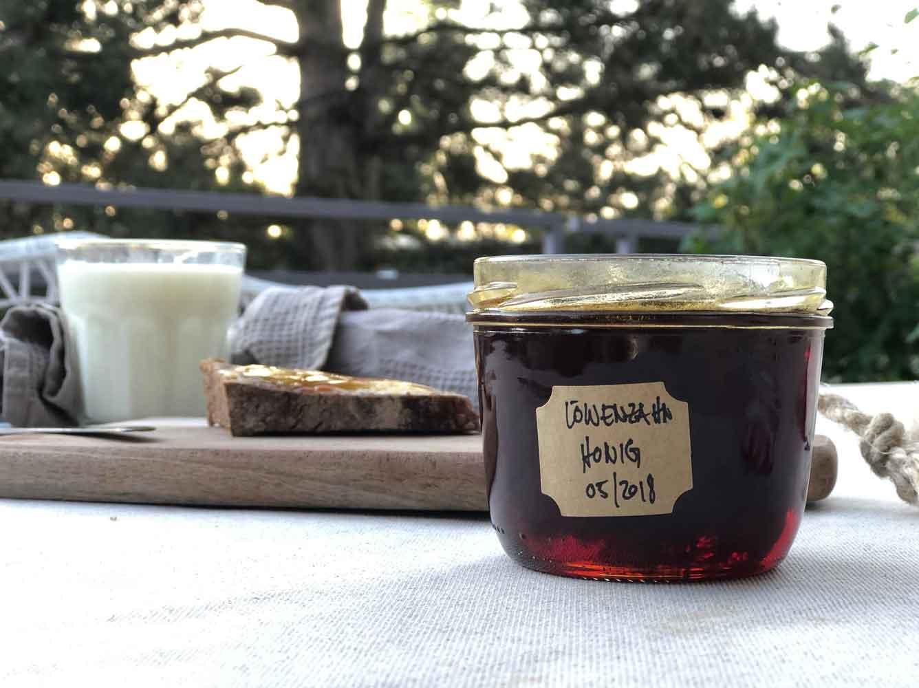 Loewenzahnhonig Terrasse Gartentisch Fruehstueck Brot Milch Honigglas - Autark leben in der Stadt | unser Pflanzenhonig aus Löwenzahn